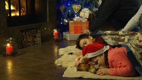 Two young children waiting for Santa Claus. Asleep on the floor in front of the Christmas tree with the parents entering to place rugs over them and lay out the stock footage