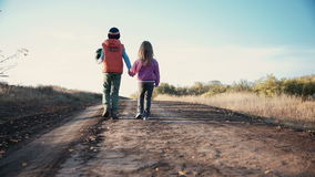 Two young children walking along a dirt road stock footage