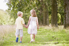 Two young children walking on path holding hands. From the back Royalty Free Stock Image
