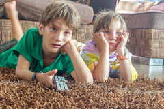 Two young children watching tv. At home Stock Image