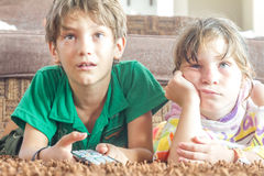 Two young children watching tv. At home Royalty Free Stock Photo