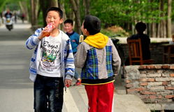 Pengzhou, China: Two Boys Walking on Road Stock Image