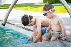 Two Young Chinese Caucasian Brothers By the Pool Wearing Swimming Goggles. Young Mixed Race Chinese and Caucasian Brothers Wearing Swimming Goggles Playing At royalty free stock photo