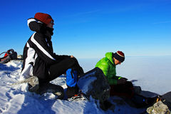 Two young climbers resting on top of Peleaga peak, Romania Royalty Free Stock Images