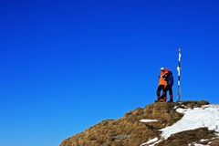 Two young climbers taking pictures on top of a peak Royalty Free Stock Images
