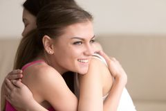Two young girlfriends embracing each other, girl smiling happily stock images