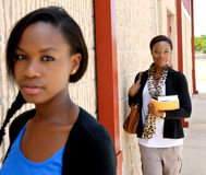 Two young college girls. Two young African college girls posed next to a wall, the girl in the foreground out of focus Stock Photos