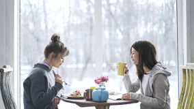 Two young college student girls eating in a cafe and talking, tilt down. Two pretty young women are eating in a cafe, drinking hot tea or coffee and having a stock footage
