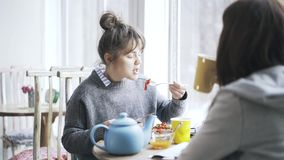 Two young college student girls eating in a cafe and talking, tilt up. Two pretty young women are eating in a cafe, drinking hot tea or coffee and having a stock footage