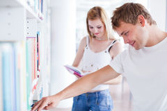 Two young college students in the library Stock Photos