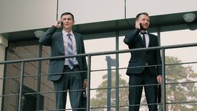 Two young confident businessmen exit the office building talking on the phones stock video footage