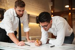 Two young confident businessmen working on a business plan. While standing over desk with graph indoors Royalty Free Stock Photo