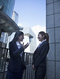 Two young confident businesswomen talking outdoors in Beijing, with CCTV building in the background Royalty Free Stock Images