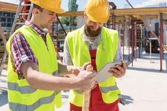 Two young construction workers smiling while using a tablet duri. Two young construction workers smiling while using a tablet for online communication through stock photo