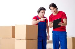 Two young contractor employees moving personal belongings. The two young contractor employees moving personal belongings royalty free stock photos