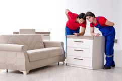 Two young contractor employees moving personal belongings. The two young contractor employees moving personal belongings royalty free stock image