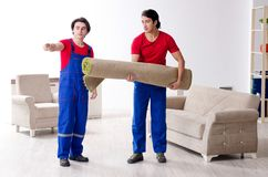Two young contractor employees moving personal belongings. The two young contractor employees moving personal belongings stock image