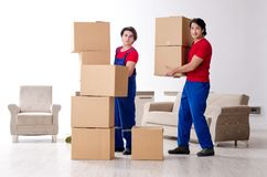 Two young contractor employees moving personal belongings. The two young contractor employees moving personal belongings stock photography