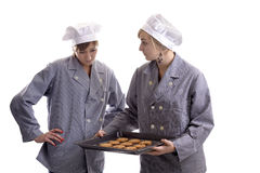 Two young cooks inspecting cookies on a plate Stock Images