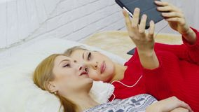 Two young cool friends listening to music on headphones through a phone lying on the bed.  stock footage