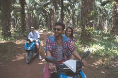 Two Young Couple Driving Scooter In Tropical Forest Cheerful Friends Group Enjoy Road Trip Together Stock Photos