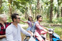 Two Young Couple Driving Scooter In Tropical Forest Cheerful Friends Group Enjoy Road Trip Together Stock Photography
