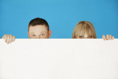 Two Young Couple Hiding on White Wall Royalty Free Stock Photography