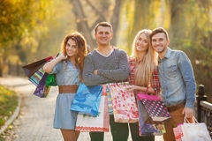 Two young couples with bags on the way to the Mall. Two young families,good friends, girls,brunette and blonde,men,both dark-haired,in a striped shirt and a Royalty Free Stock Photos