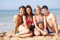 Two young couples on beach holiday Stock Photos