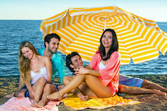 Two young couples on a beach under an umbrella. Stock Photography