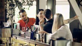 Two young couples drinking cocktails at the bar counter talking and laughing.Four friends spending time chattering with. Two young couples are drinking cocktails stock video