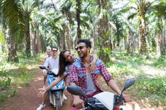 Two Young Couples Driving Scooter Bike In Tropical Forest Young Group Of People Making Road Trip In Palm Trees Wood. Together Youth And Vacation Concept stock photo