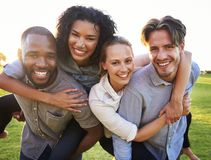 Two young couples having fun piggybacking outdoors Stock Photography