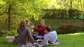 Two young couples picnicking in an autumn park