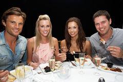 Two young couples in restaurant. Smiling royalty free stock photos