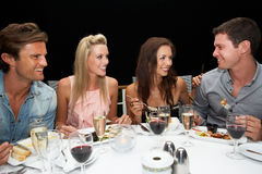 Two young couples in restaurant. Smiling royalty free stock images