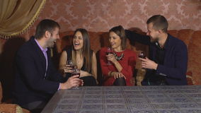 Two young couples in restaurant. Two young couples resting in the restaurant,drinking and talking, slow motion stock video