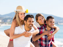 Two young couples on sand beach. Two young smiling couples having fun on sandy beach at summer day. Selective focus royalty free stock photos