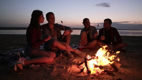 Two young couples are sitting on the beach near the bonfire. Roasting meat on wooden sticks, eating. Happy time together. Picnic. Evening dusk stock footage