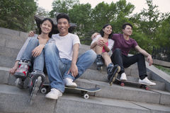 Two young couples sitting and resting on concrete steps outside with skateboards and roller blades Stock Photos