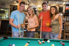 Two young couples standing beside a pool table Royalty Free Stock Photos