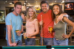 Two young couples standing beside a pool table stock photo