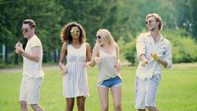 Two young couples in white clothes dancing, enjoying music, having fun outdoors. Stock footage stock video footage