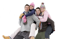 Two young couples in winter clothing, portrait, men carrying women on backs, cut out Royalty Free Stock Photo