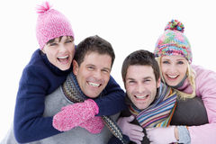 Two young couples in winter clothing, portrait, men carrying women on backs, cut out royalty free stock images