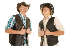Two young cowboys hold vests. Two teen cowboys in their western hats showing some attitude stock photography