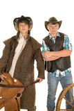 Two young cowboys with saddle and wagon wheel. Two young cowboys with serious expressions on their faces royalty free stock image