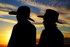 Two young cowboys silhouette wearing hats with a s. Young cowboys silhouette wearing hats sunset background royalty free stock photo