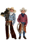 Two young cowboys wearing chaps holding a saddle a Stock Images