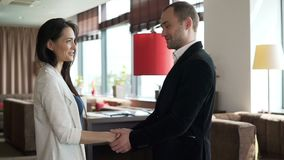 Two young coworkers shake hands after meeting. Two young coworkers shake hands after meet. Male and female successful adult person signed a contract between stock video